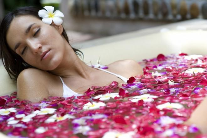 Девушка расслабилась в ванне с лепестками роз